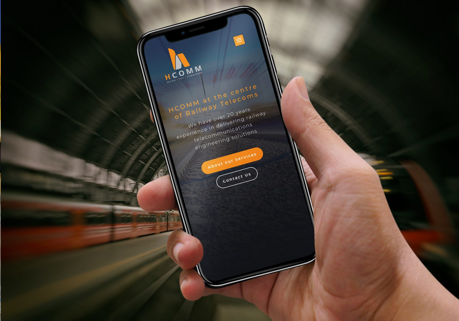Hcomm's new website on a mobile phone with trains in the background